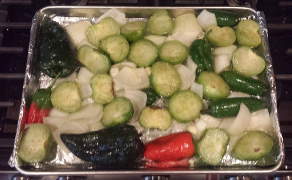 Tomatillos, jalapenos, poblanos, bell peppers, onions and garlic before being roasted.