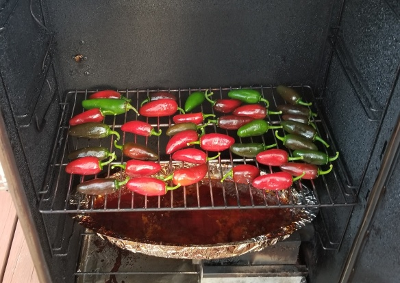 Jalapenos being put into the smoker.